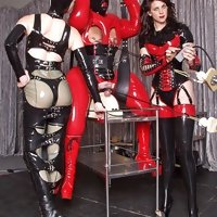 Two dommes in latex training their sissy slave in rubber doll suit