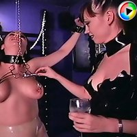 Young mistress in latex dress trains a bondaged woman clasping her nipples