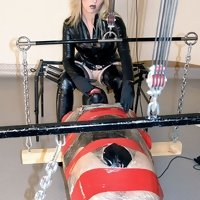 Rubber clad Mistress Sidonia makes her slave pleasure her while he's cocooned in clingfilm.