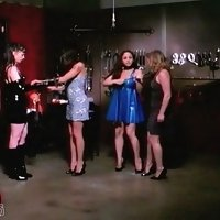 Strict dominas train two female slaves in bondage whipping their round asses